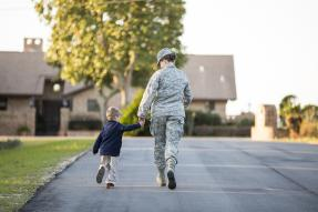 Woman in military fatigues and child walking toward house