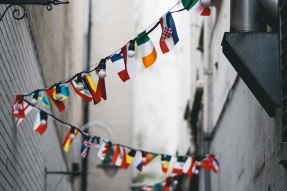 Narrow european street with international flag garland