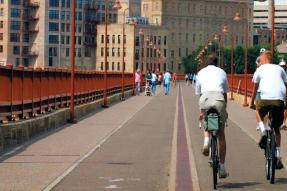 Two men riding a bicycle over a pedestrian bridge in downtown Minneapolis