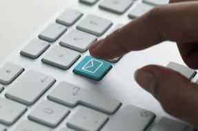 Person about to touch email button on keyboard