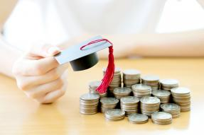 Person holding a tiny mortarboard over stacks of coins