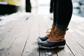 Person wearing snow boots on a deck