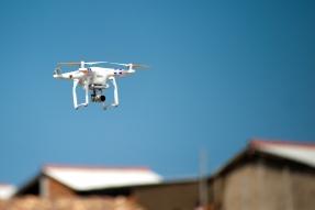 drone flies over rooftops