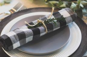 A plaid napkin sitting on top of a gray plate and white with black rim charger