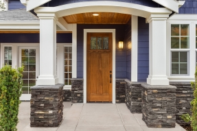 Porch of dark blue house with pillars