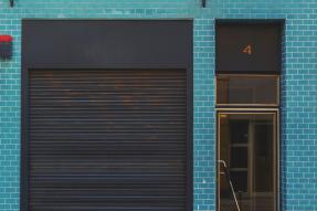 A Blue building with a sliding garage door on front
