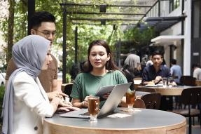 Professional woman and two clients looking at a laptop in a sidewalk cafe