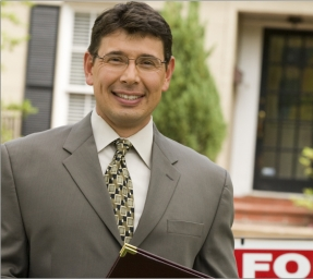 Appraiser standing in front of a house for sale