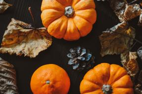 Pumpkins and fall leaves on a black table