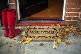 Red boots next to a welcome mat and an open door