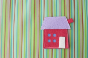 Red felt house on striped background