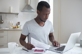 Serious young man at laptop, with papers, calculator