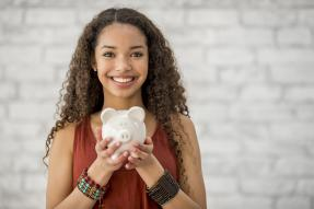 Smiling young woman holding a piggy bank