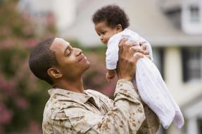 Soldier holding a baby in front of house