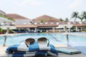 Sunglasses, towel, and phone next to a pool at a resort
