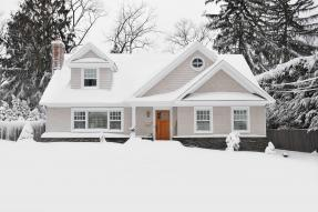 Tan shingled house with wood door in the snow