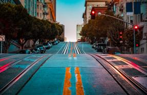 Twilight view of an empty road with cable car tracks leading up a steep hill on street at dawn, San Francisco, CA