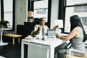 Two women having a conversation at a desk in an office
