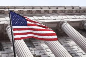 U.S. flag in front of a building with pillars