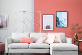White couch in foreground, with a wall painted half white, half coral