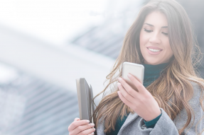 Woman holding a portfolio and looking at phone