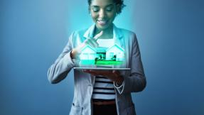 A Woman holding a holographic house in her hands, and smiling