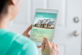 Woman looking at a residential listing on a tablet
