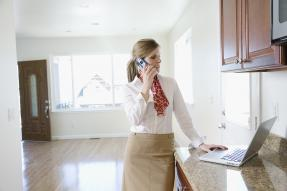 Woman on the phone in an empty house with the door open