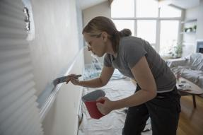 Woman painting a wall above a chair rail