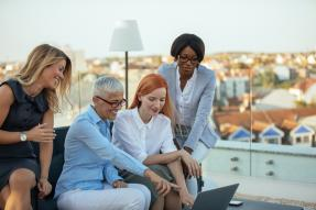 four women professionals looking at laptop