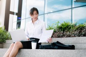 Young professional woman seated on steps with laptop and coffee
