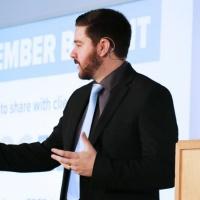 Aleksandar Velkoski presenting on stage at an event.
