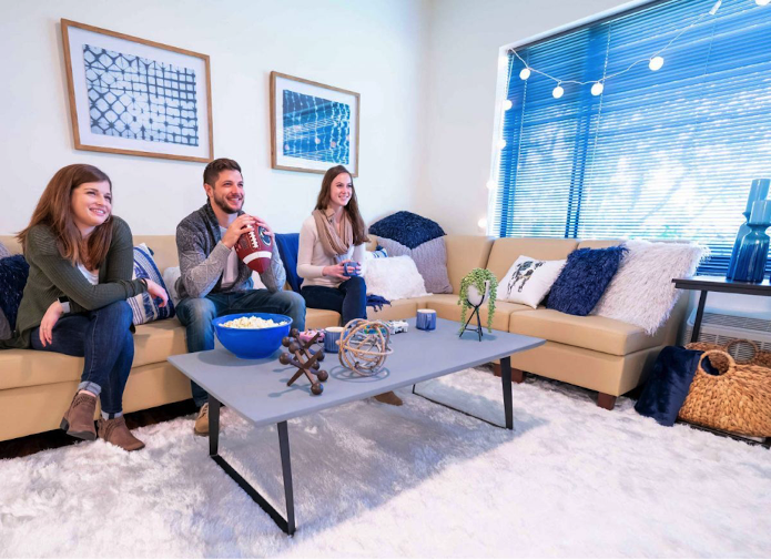 3 people sitting at couches in a living room, with a white carpet.