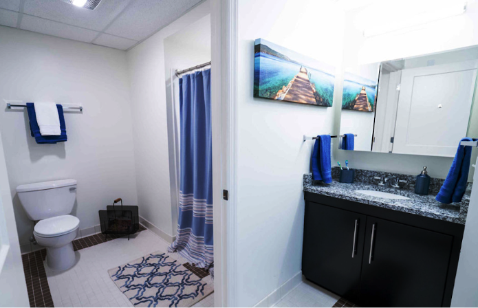 A staged dorm bathroom with blue details.