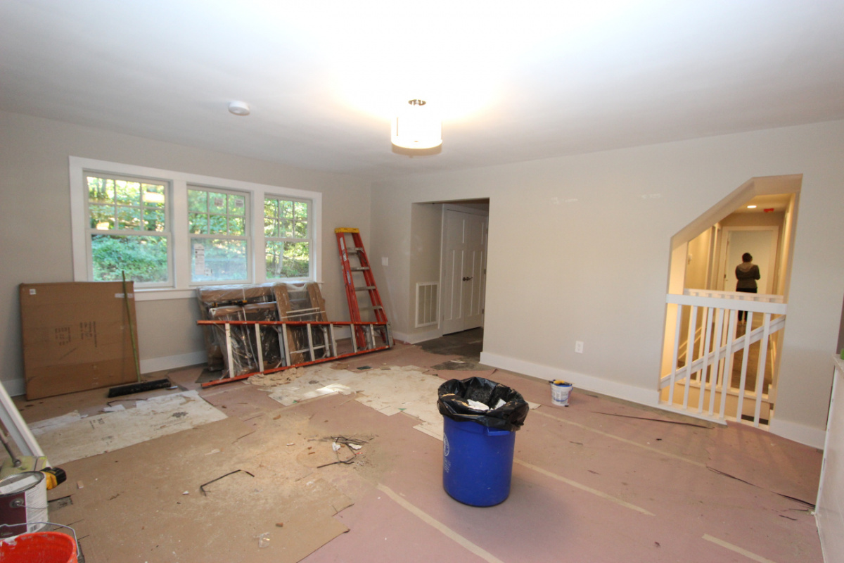 A dining room under heavy renovation, with no flooring, and contracting supplies