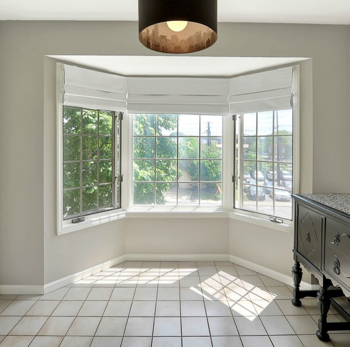 A house interior, looking out a bay window with white tile floor and a shaded ceiling fixture