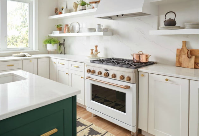 A kitchen with white cabinets and a stovetop with gold colored handles and hardware