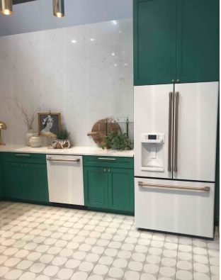 A Kitchen with white tile, walls, and alternating green cabinets, and appliances with gold colored hardware
