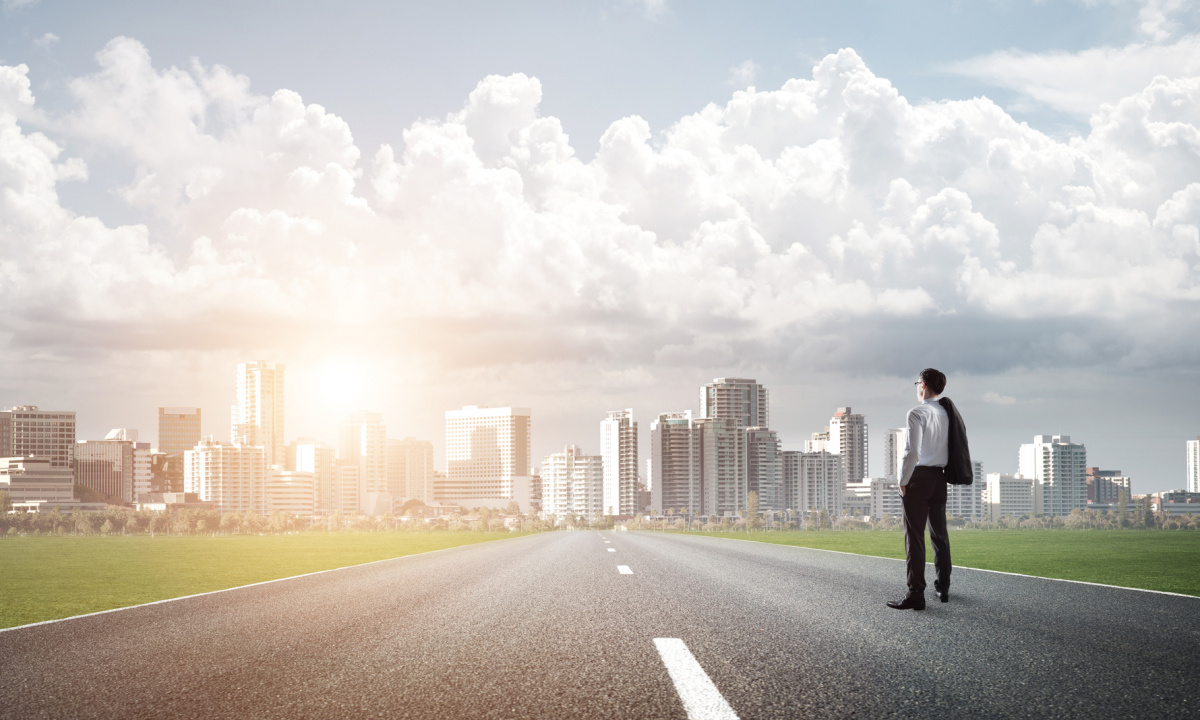 Man standing on highway looking at city in distance