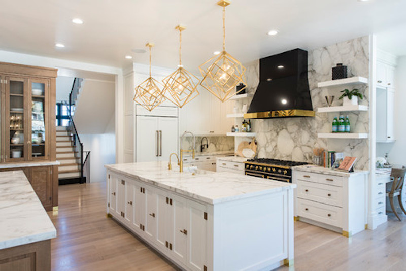 Kitchen showing black exhaust hood with gold colored trimming
