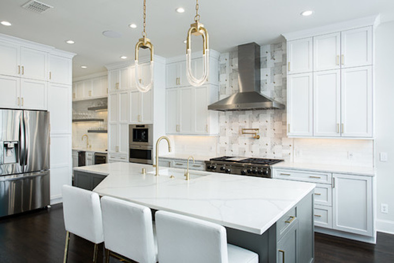An all white kitchen with stainless steel hood