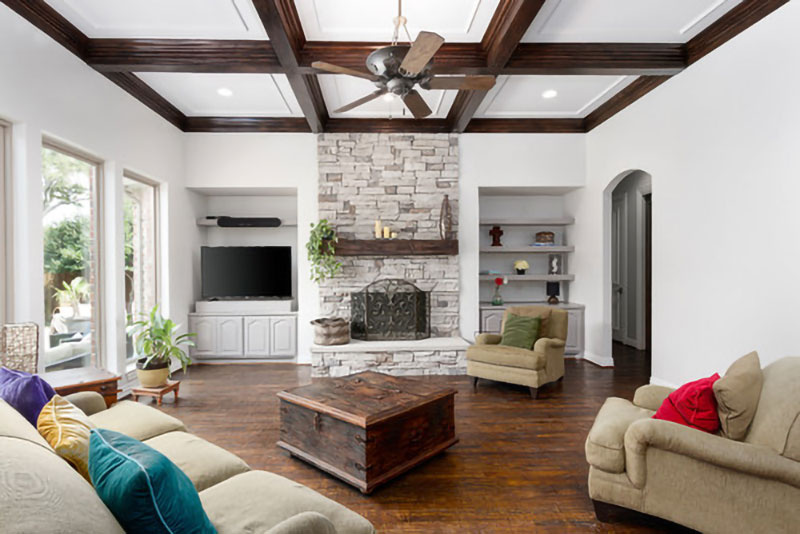 A living room with exposed beams, hardwood floor and coffee table and couches, in white.
