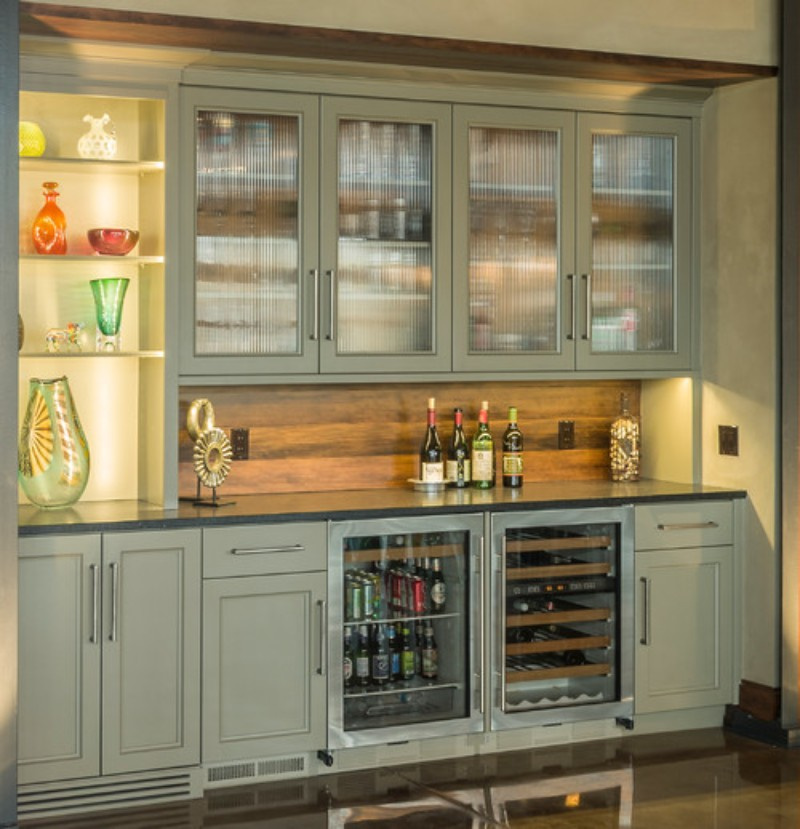 A home bar, with win fridge, glass cabinets, and white cabinets with stainless steel bar hardware
