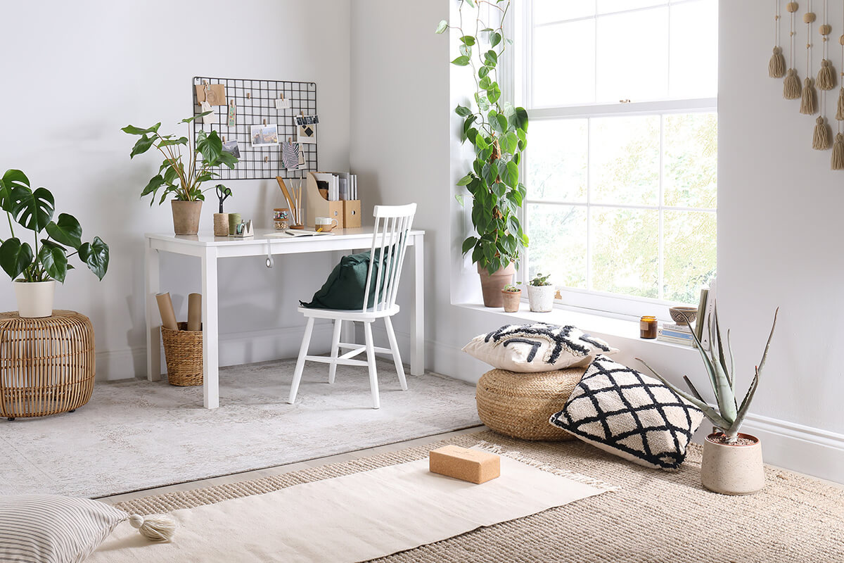 A light colored corner of a room with throw pillows on the floor, a desk and chair, accented by potted green house plants.