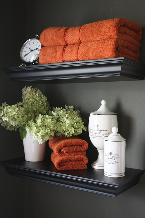 A set of bathroom shelves with orange towels