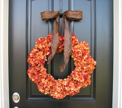 A orange fall wreath on a door