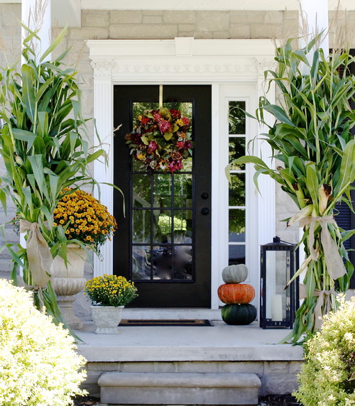 A front porch with some pumpkins as fall decorations