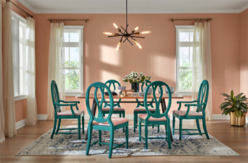 "A Rose ""Blush"" color painted dining room with teal-green chairs around a table."