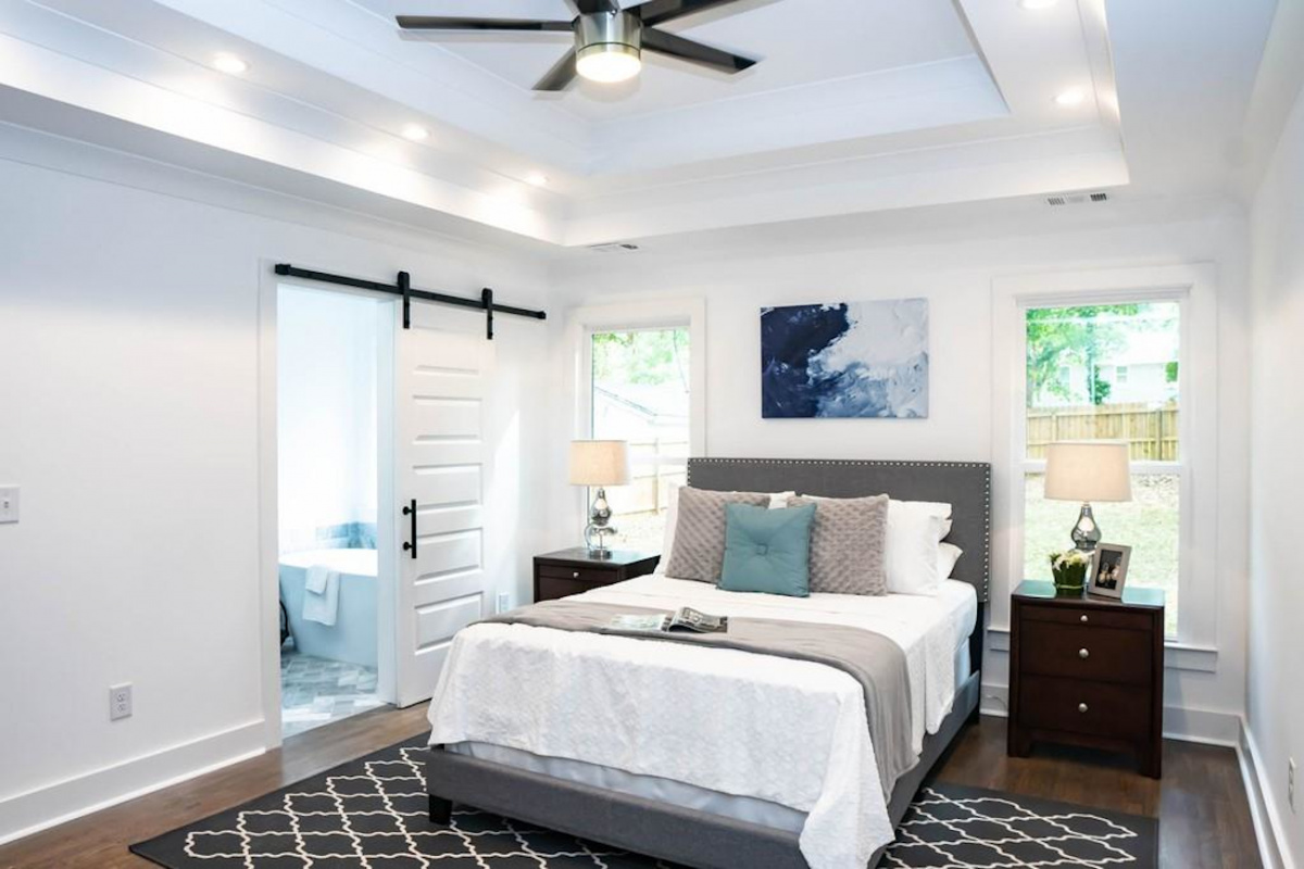A bedroom with earth tone colored rug and pillows against white walls and bed comforter