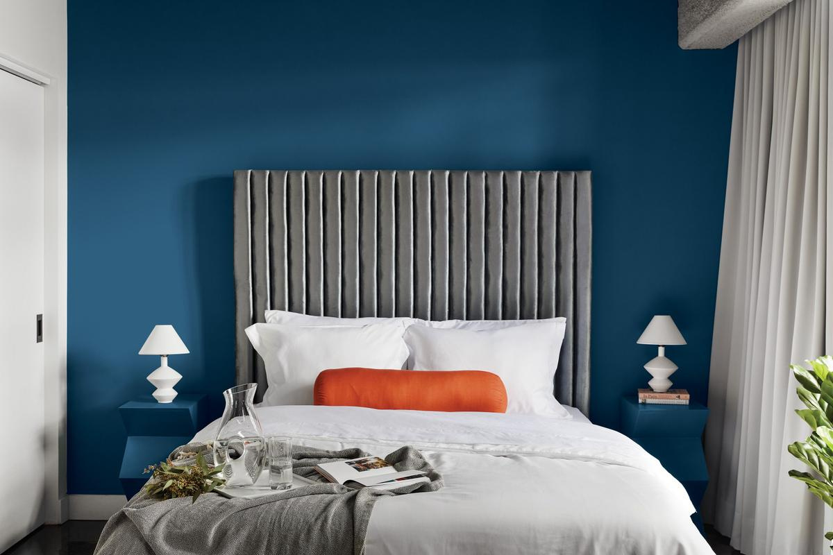A bedroom, containing a bed with a large headboard against a blue wall, flanked on both sides by blue nightstands